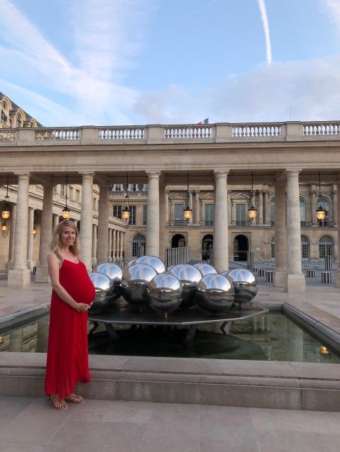 Blonde girl pregnant in red dress in Paris