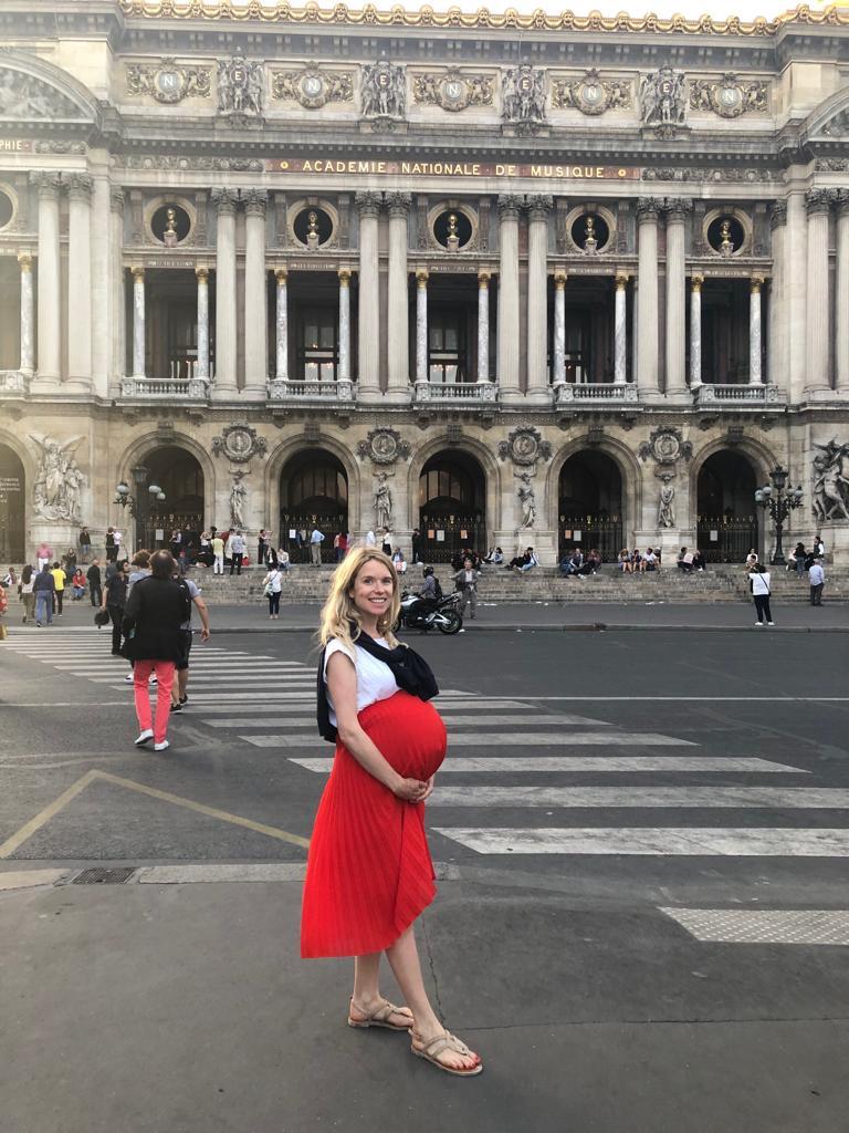 Blonde girl pregnant in red skirt in Paris
