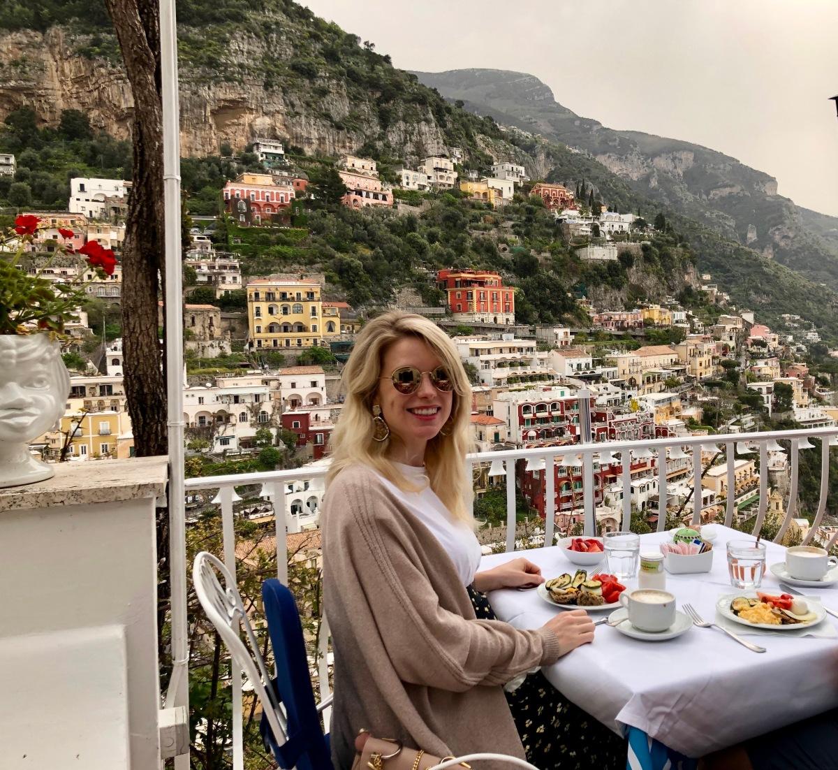 Blonde girl eating breakfast in Positano Italy Amalfi Coast